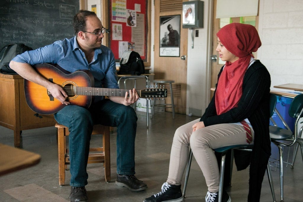 Teaching artist Ami Yares playing guitar with a singing student in a classroom