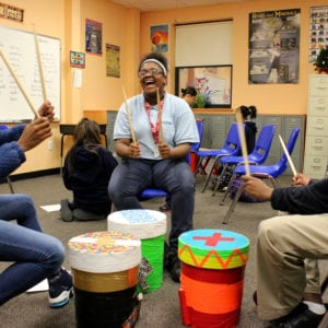 Three laughing students playing their bucket drums in a classroom