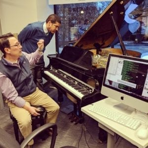 ExCITe Center director Youngmoo Kim demonstrates the ExCITe Center's magnetic resonator piano. Youngmoo sits on the piano bench, while composer Jay Fluellen looks into the open lid of a baby grand piano. There is a computer monitor and keyboard next to the piano keyboard.
