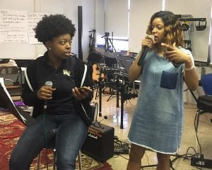 "Grammy-nominated songwriter Kristal ""Tytewriter"" Oliver (right) coaches high school student Bria from Hill-Freedman World Academy. They are holding microphones and talking to each other, in a classroom full of instruments and sound equipment."