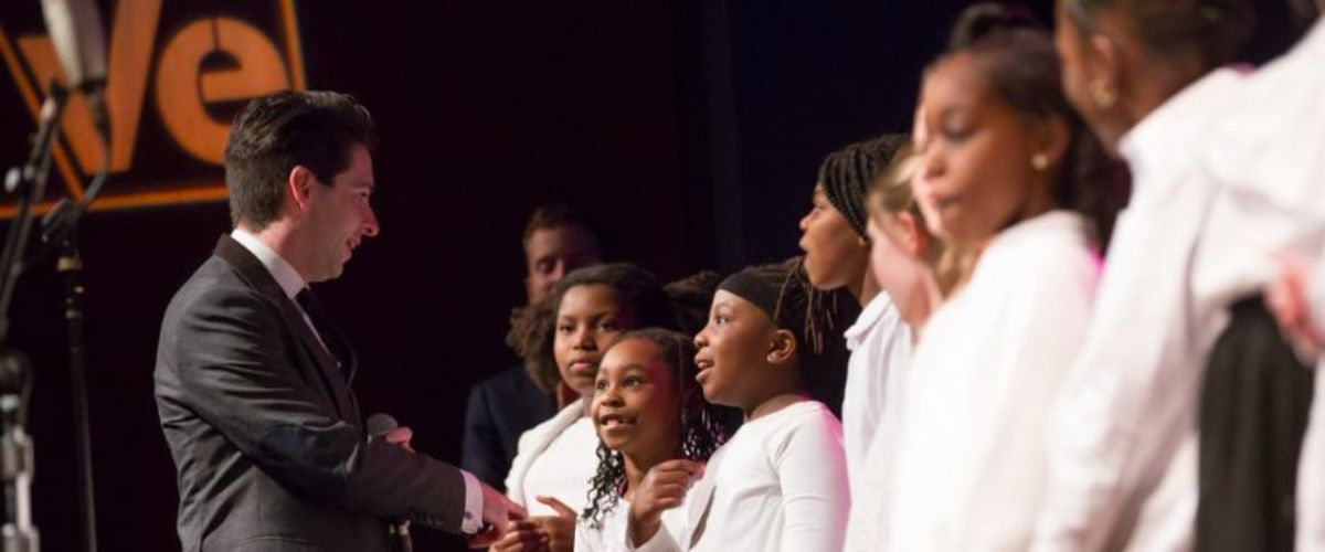 Paul Smith (left) of VOCES8 talks on stage with elementary students from C.W. Henry School. About 8 students are standing in a line, wearing matching white shirts, and one girl is pointing to herself with excitement as Paul gestures toward her.