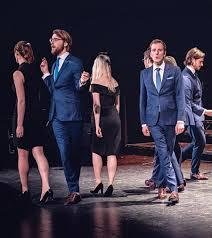 The members of VOCES8 walk different directions across a stage while singing, dressed in black dresses and blue suits.