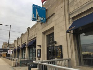 The entrance to World Cafe Live. A blue square sign hangs above the front entrance with the World Cafe Live logo.