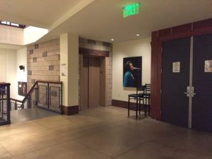 The mezzanine lobby at World Cafe Live. To the left is the top of the stairs leading to the lower level. To the right of the stairs is the elevator, and along the wall lies a portrait of an artist. On the left of the picture is the entrance to the mezzanine of Downstairs Live.