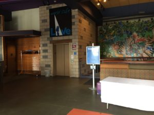 The top floor lobby of World Cafe Live. To the right is the bathroom entrance, in the middle is an elevator. Above the elevator is the World Cafe Live logo. To the right is a staircase, behind the staircase is a mural of the top of a tree.