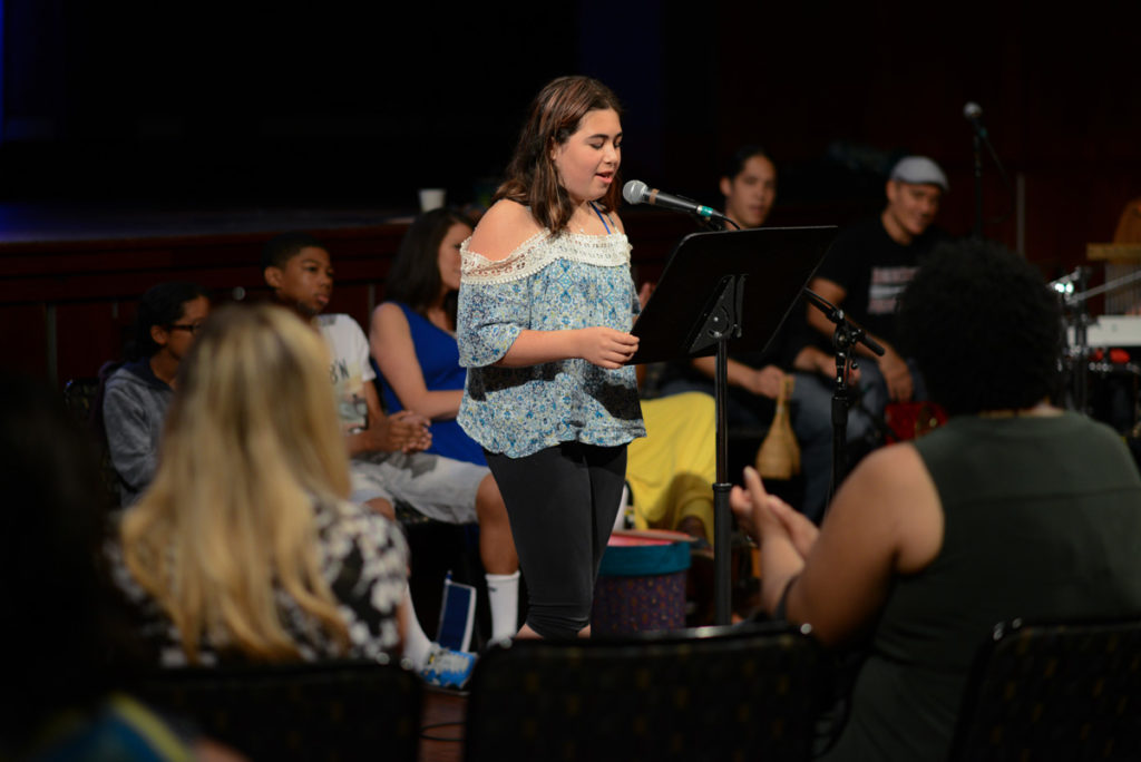 Samantha, a student from The Center for Grieving Children, stands in front of other students attending the Percussion Studio as she recites her poem into a microphone.