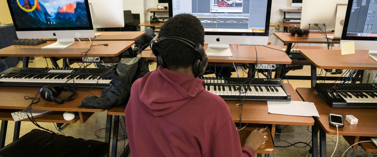 A student works on producing his own tracks in the music technology lab at Hill-Freedman World Academy.