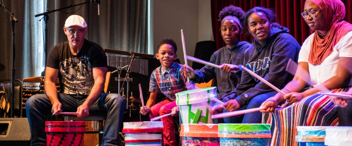 Josh Robinson, left, watches on as Percussion Studio students play call and response with their beats.