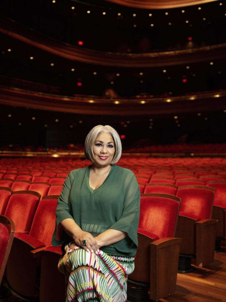 Dyana Williams sits at the edge of a row of seats in the audience of a theater.