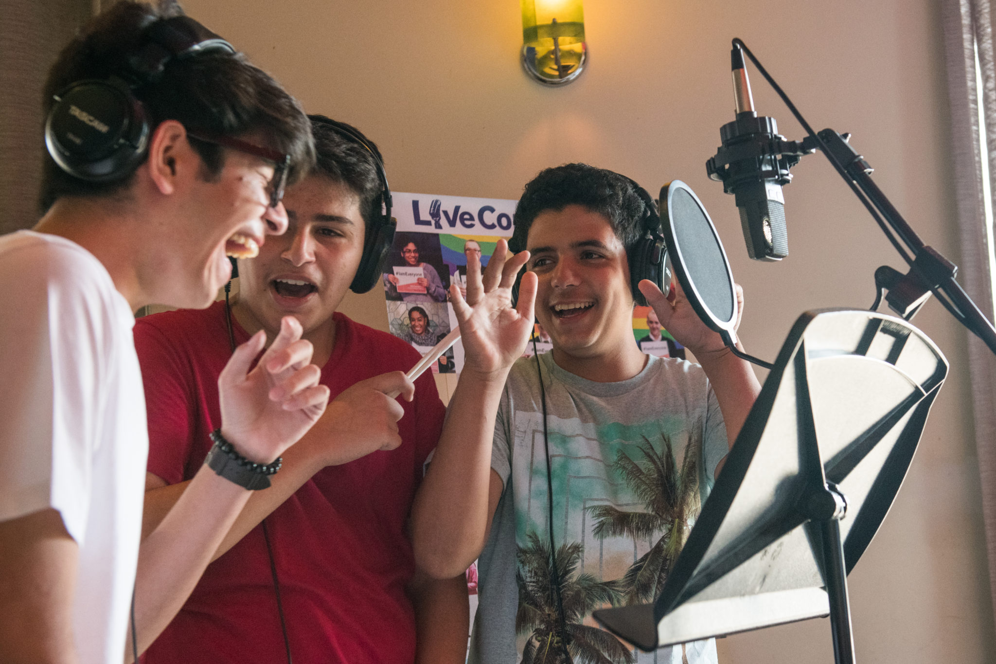 Three boys wearing over the ear headphones and stand behind a recording microphone and a music stand. They're gesturing and laughing among themselves