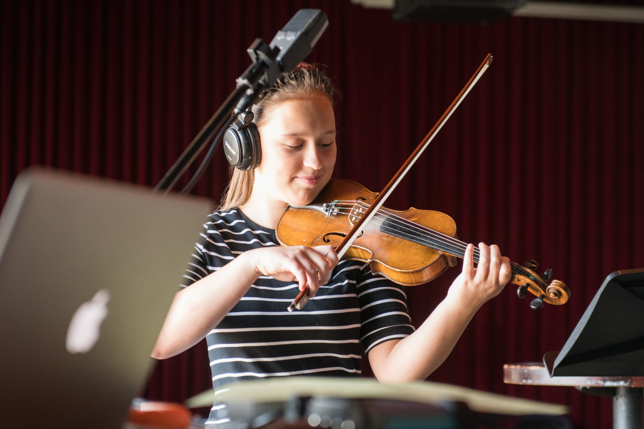 A student wears over the headphones as she plays violin behind a recording microphone.