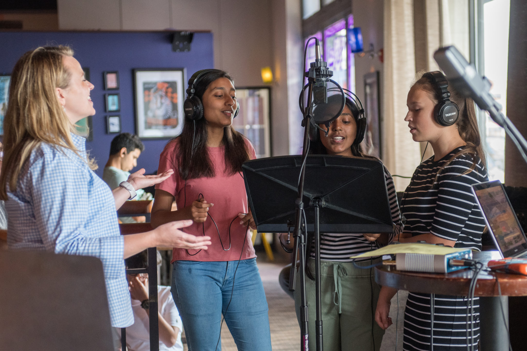 Teaching artist Blair Bodine stands to the left, leading three students to the right in recording a song. The students are wearing over the ear headphones and singing to a recording microphone.