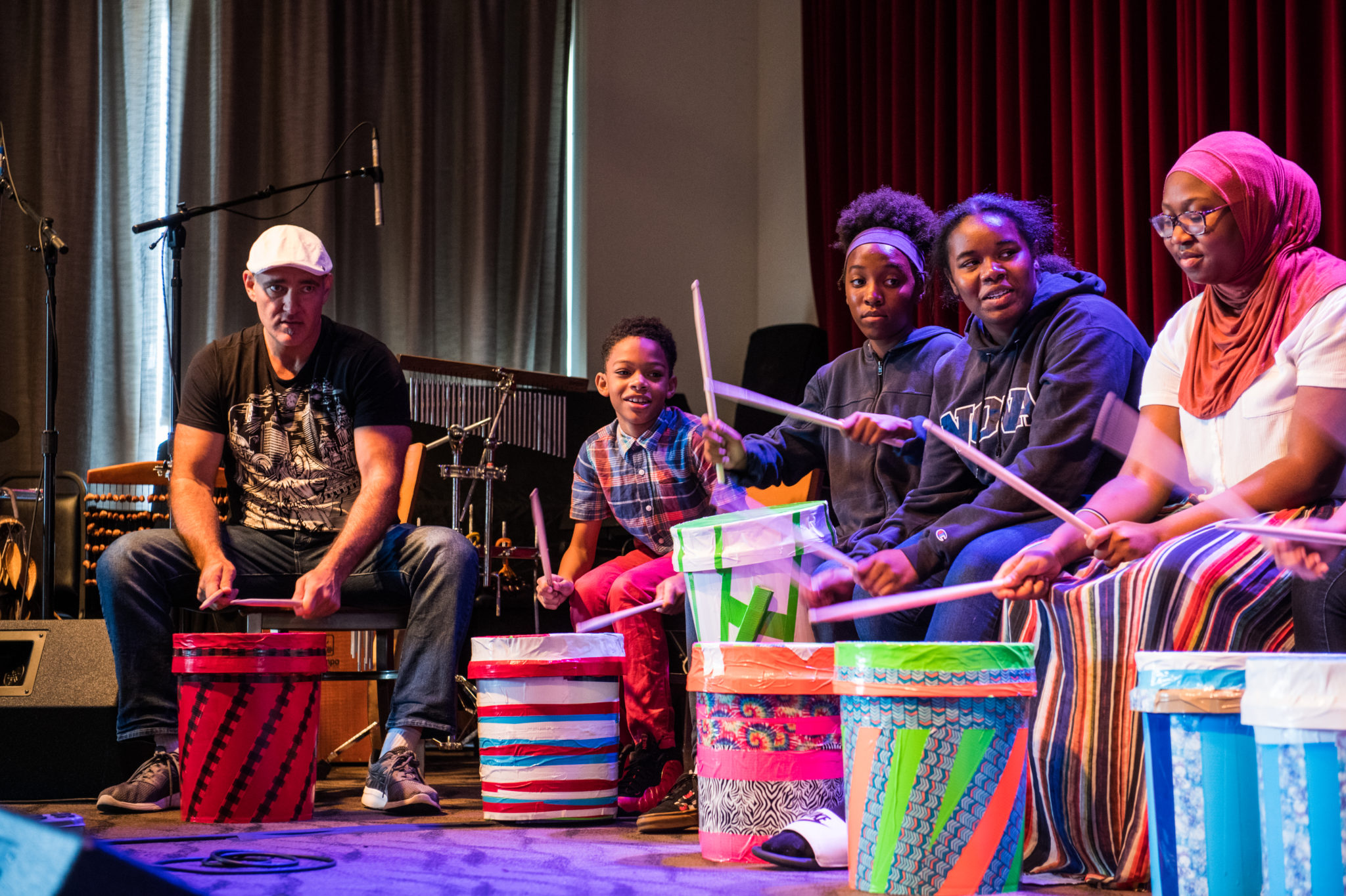 Josh Robinson sits on the left of the stage leading students in a bucket drumming exercise. To his right, four students sit behind their bucket drums, following along.