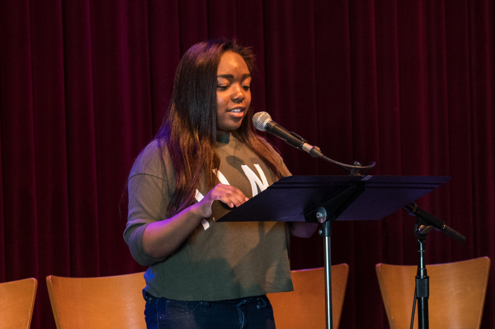 A student stands behind a mic and a music stand to present her poem onstage.