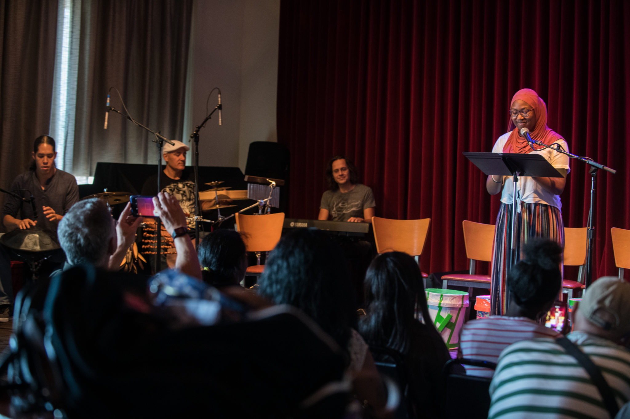 A student stands behind a mic and a music stand onstage to present her poem. To her left are Alex Shaw, Josh Robinson and Andrew Lipke accompanying her. In the foreground, an audience looks on.