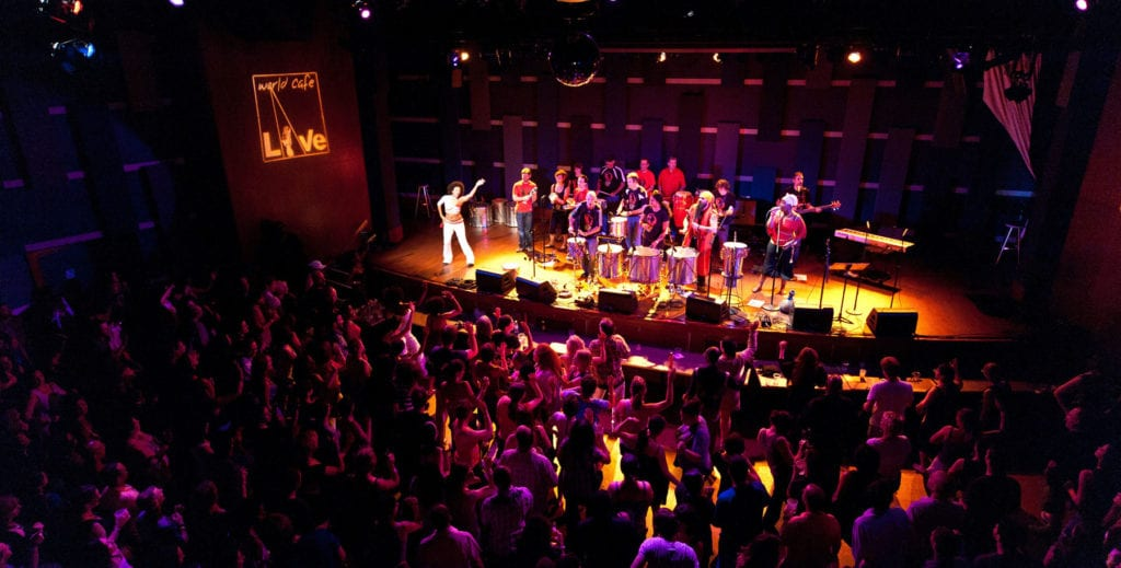 Image of band on stage at WCL in front of a full audience.